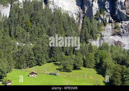 A rocky mountain and waterfall as seen from Lauterbrunnen , below is a forest and meadow and there are huts and - Stock Image