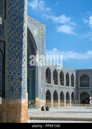Isfahan, Iran - March 3, 2017 : two men sitting in the yard of Shah Mosque, also known as Imam Mosque. It is a UNESCO World Heritage Site - Stock Image