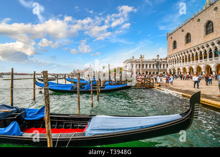 Gondolas line the Grand Canal station as tourists pass by the Doge's Palace and St. Mark's Square with the Santa Maria Della Salute dome behind - Stock Image