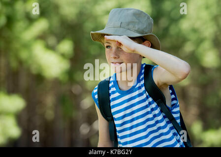 Boy shading eyes while exploring outdoors - Stock Image