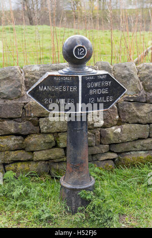 Cast iron milepost 12 on the Rochdale canal in the village of Walsden near Todmorden on the Lancashire/Yorkshire - Stock Image