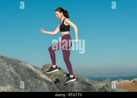woman running across rocks, cross country, fitness - Stock Image