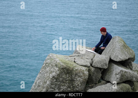 A landscape painter sketching in Cornwall,UK - Stock Image