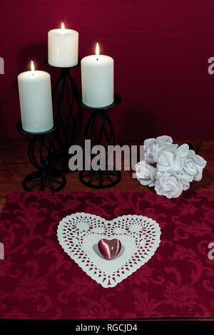 Heart shapped dollie and gemstone, three white candles in metal holoders and bouquet of white roses on wooden table. - Stock Image