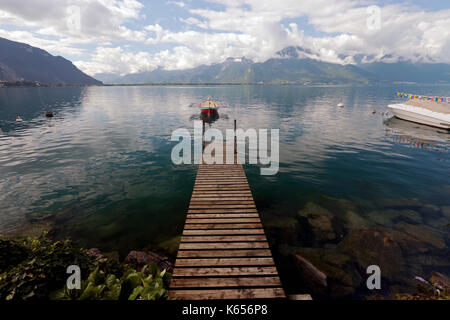 Walkway, pier or gangplank leading to rowing boat on Lake Geneva near Montreux in Switzerland on a sunny day with - Stock Image