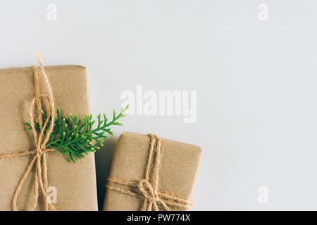 Two Gift Boxes Wrapped in Craft Paper with Juniper Twig on White Background. Christmas New Years Presents Shopping Sale. Copy Space. Poster Banner Cou - Stock Image