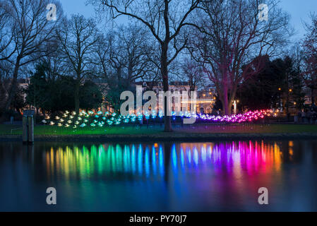 Colorful night in Amsterdam, Wertheimpark during the Amsterdam Light Festival with the artwork On the Wings of Freedom of Aether & Hemera. - Stock Image