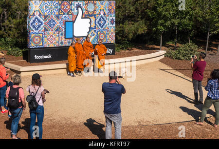 Facebook HeadquartersThumbs Up Sign with Buddhist Monks and other tourists taking pictures at the entrance at 1 - Stock Image