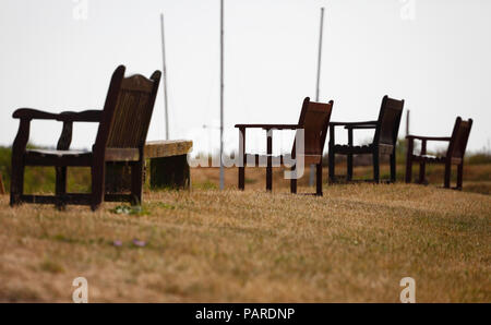 Wooden benches facing the sea at Burnham Overy Staithe on the Norfolk coast. - Stock Image