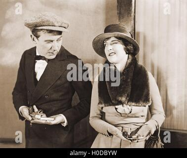 Winking gangster with his gun moll - Stock Image