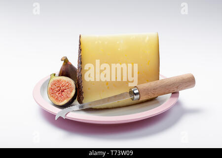 Piece of Spanish hard scheep milk cheese Manchego on white board served with fresh ripe figs and cheese knife, close up isolated - Stock Image