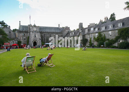 Relaxing in deckchairs during a summer fete on the front lawn of Darlington Hall with the Great hall behind,Totnes, Devon, England, UK - Stock Image