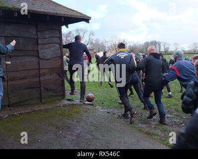 Ashbourne Shrovetide Football 2019. A sight of the ball as play enters the town playing fields during the Ash Wednesday match. - Stock Image