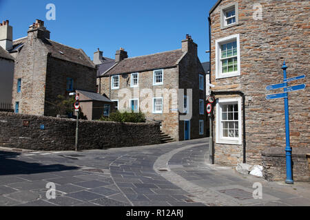 Old sandstone houses in Stromness, Orkney with paving stones from a local quarry and cobble stones in the centre of the street. - Stock Image
