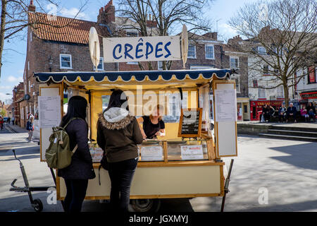 Two young women buy crêpes crepes at a stree food stall in York, UK. - Stock Image