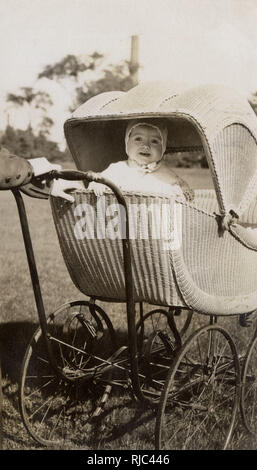 Lloyd Loom perambulator with a sweet young occupant! - Stock Image