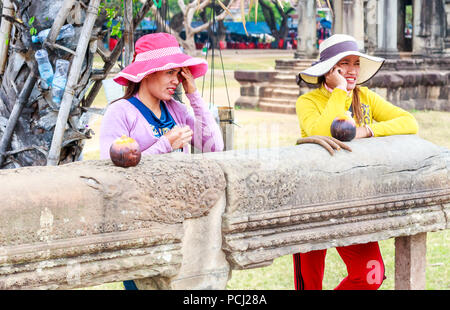 Angkor Wat, Cambodia - 11th January 2018: Two Cambodian girl vendors wearing hats. There are many vendors around the complex. - Stock Image