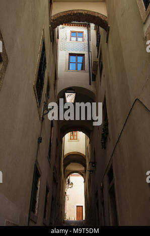 Walls and windows flanking, and topping a narrow and tall archway in Alfama disctrict, the most famous and ancient typical neighborhood of Lisbon. Por - Stock Image