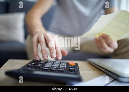 Human hand over calculator touching buttons while counting total sum of monthly home payment bill - Stock Image