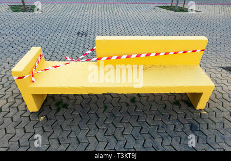 A yellow stone bench that's been freshly painted in Alameda de Hercules in Seville - Stock Image
