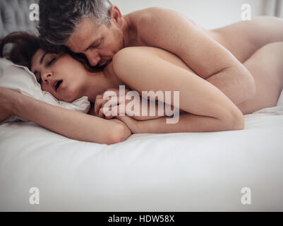 Passionate couple in bed having sex. Young man and woman making love in bedroom. - Stock Image