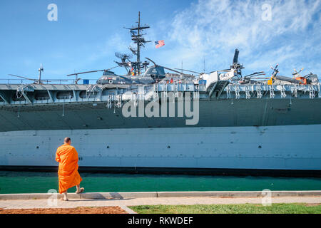 A monk on his phone at the USS Midway Museum. - Stock Image