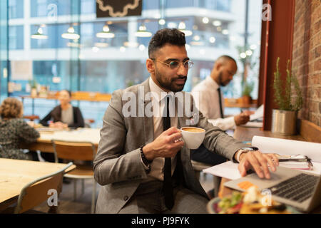 Focused businessman drinking coffee and working at laptop in cafe - Stock Image