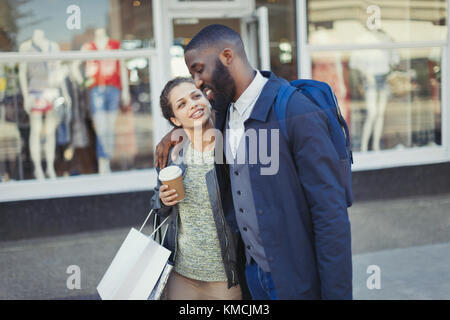 Affectionate young couple with coffee and shopping bag outside storefront - Stock Image