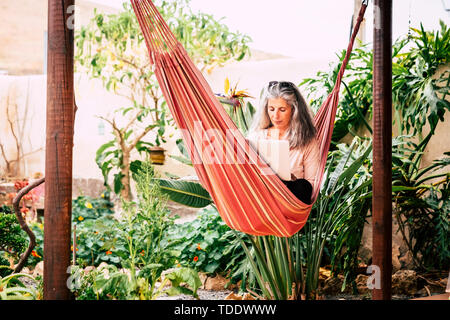 Relax on hammock for alternative people - young woman with long grey white hair use a laptop computer outdoor in the garden - technology and internet  - Stock Image