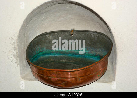 holy water in an old stoup made of copper with verdigris in the inside attached to a wall niche in a church, stoup with clear holy water in a bavarian - Stock Image