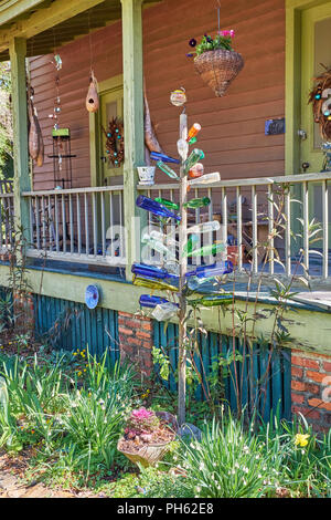 Folk art bottle tree with colorful bottles as garden art in Old Alabama Town, Montgomery Alabama USA. - Stock Image