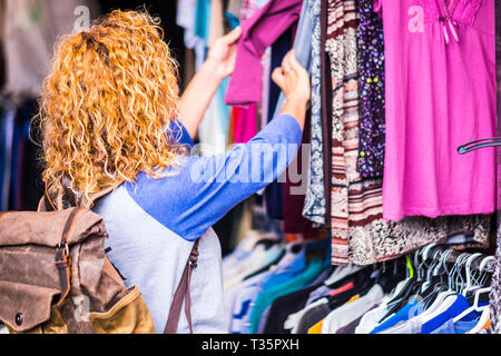 Blonde curly woman at the market choosing clothes - colours and alternative travel vacation experience for backpackers people - different lifestyle co - Stock Image