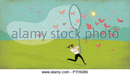 Woman chasing heart butterflies with net - Stock Image