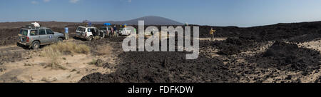 Four Landcruisers stop in the middle of jagged black basalt lava fields near Erta Ale, in a ring of other volcanoes, - Stock Image