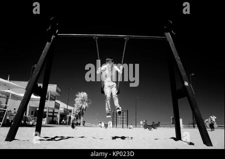 Child swinging in Castellon, Spain. - Stock Image