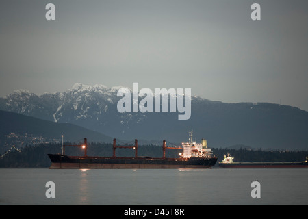 Cargo freighters anchored in English Bay, Burrard Inlet, Vancouver, British Columbia, Canada - Stock Image