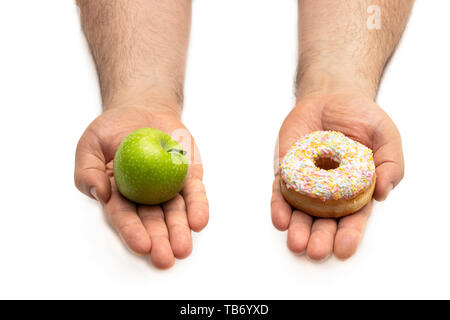 Hands  holding an apple and a doughnut concept of a tough choice between opposite alternatives (healthy food vs sweet food) - Stock Image
