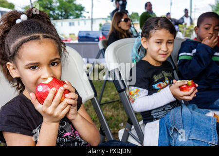 Miami Florida Overtown Hispanic Black girl girls boy eating eat apple fruit lunch health bite - Stock Image