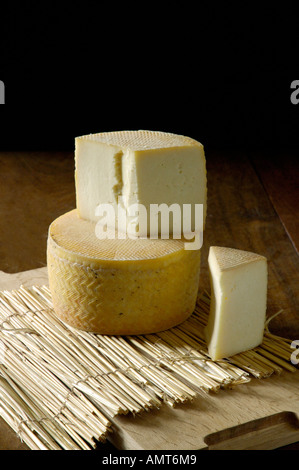 Cheese rounds on rustic table - Stock Image