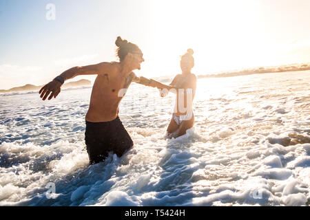 Beautiful caucasian couple enjoy the summer day of vacation with sunlight in background playing and having fun in the sea - people in bikini holiday e - Stock Image