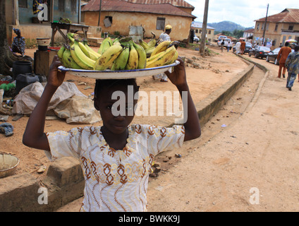 A Nigerian girl child works by hawking plantain to help with family upkeep along the street in Ikoro Ekiti, Nigeria. - Stock Image