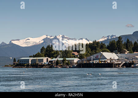 The main fishing port in the tiny village of Petersburg on Mitkof Island along the Wrangell Narrows in Frederick Sound with the Alaska Coast Range of mountains behind on Mitkof Island, Alaska. Petersburg settled by Norwegian immigrant Peter Buschmann is known as Little Norway due to the high percentage of people of Scandinavian origin. - Stock Image