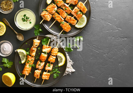 Bbq salmon kebab. Barbecue salmon skewers on black stone background with copy space. Top view, flat lay - Stock Image