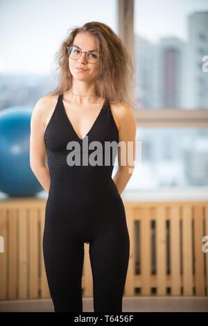 Young pretty woman in glasses standing in the fitness studio - Stock Image