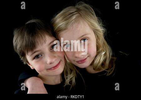 Portrait of two young sisters hugging each other - Stock Image