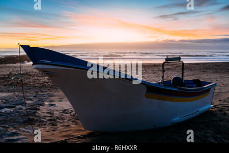 Traditional wooden fishing boat on sand at Caparica beach, near Lisbon, Portugal. - Stock Image