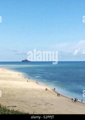 A long distance view of a white sandy beach on a tropical island with people walking along the coast of a blue and calm ocean in Cornwall - Stock Image