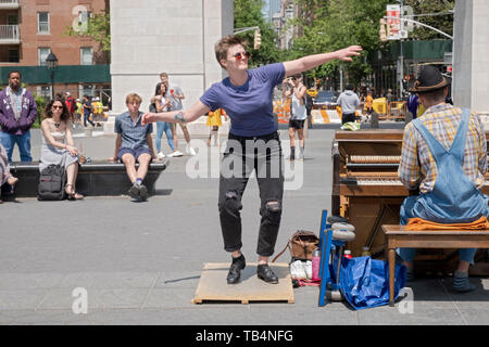 A pretty tap dancer and a piano player perform together near the arch in Washington Square Park in Manhattan, New York City. - Stock Image