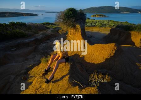 Alone in nature wilderness sitting blonde young woman wearing little Black dress fishnet tights and high-heels shoes - Stock Image