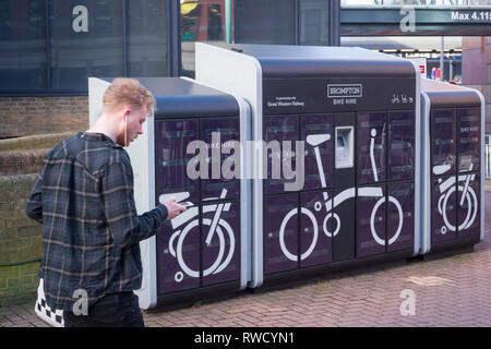 A young man on his phone passes the Brompton Bike Hire dock outside Reading Station, Berkshire. - Stock Image
